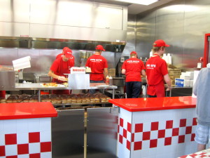 Five Guys employees making burgers for hungry customers